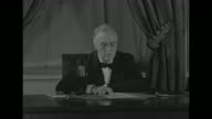 US President Franklin Roosevelt sits at desk in black tie and pince nez microphone stands on desk window stands in background with brocaded curtains...