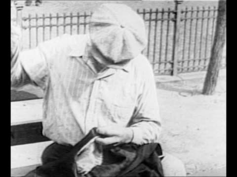 US President Franklin Roosevelt speaks / man sits on park bench mends piece of clothing with needle and thread during the Great Depression / montage...