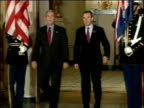 President George W Bush and Tony Blair walk along red carpet to face press White House Nov 04