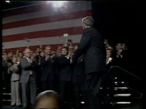 US President George W Bush arrival at rally and up to stage / Bush waving on stage zoom in as he's in front of US flag / Bush making speech / Bush...