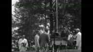 President Herbert Hoover arrives on outdoor platform festooned with banners American flags many men and women seated on platform / VS Hoover at...