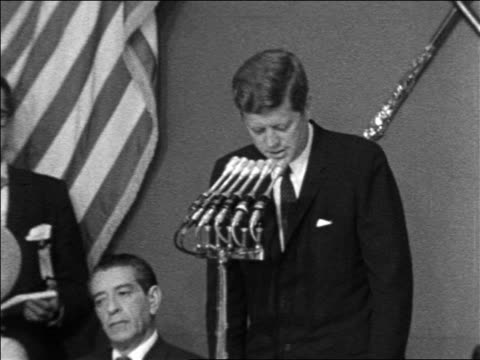 President John Kennedy making speech looking down / Mexican president sitting next to him