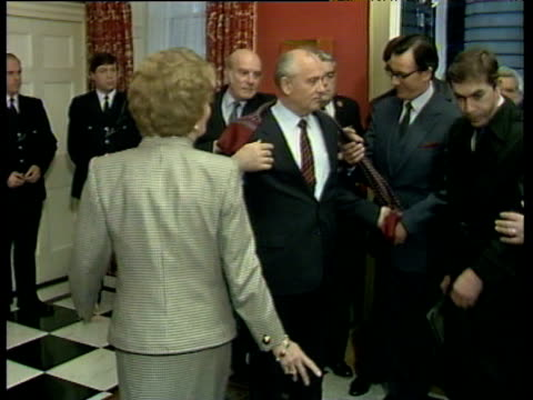 President Mikhail Gorbachev takes off coat and scarf Prime Minister Margaret Thatcher leads him to fireplace where they pose for photographers inside...