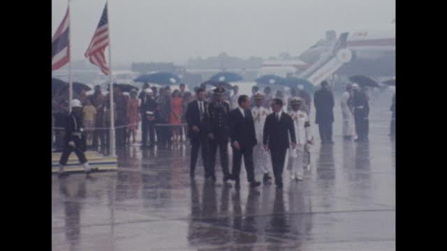 President Nixon and King Bhumibol walk together at an airport in Bangkok