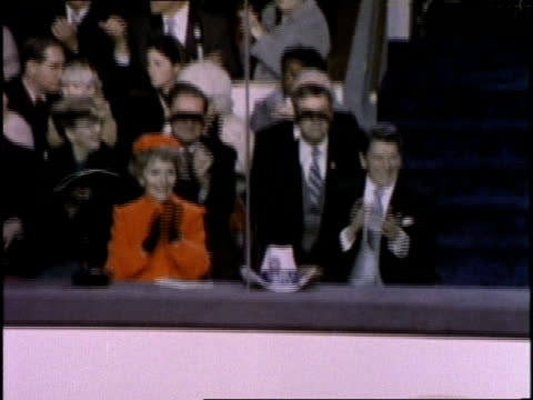 US President Ronald Reagan and his wife Nancy clap during Reagan's inauguration ceremony in Washington DC