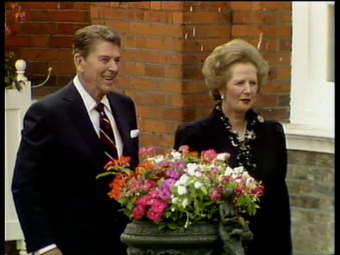 President Ronald Reagan and Prime Minister Margaret Thatcher walk outside Kensington Palace Reagan shakes hand with royal guard London 04 Jun 84