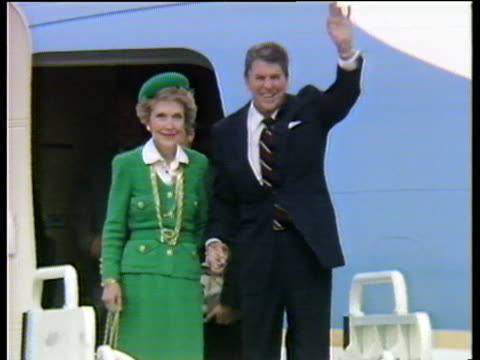 President Ronald Reagan and wife Nancy wave and walk down steps of plane as they arrive in London 04 Jun 84