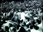 President Sukarno standing in opentop car and waving as it moves through large crowd of cheering supporters / Indonesia
