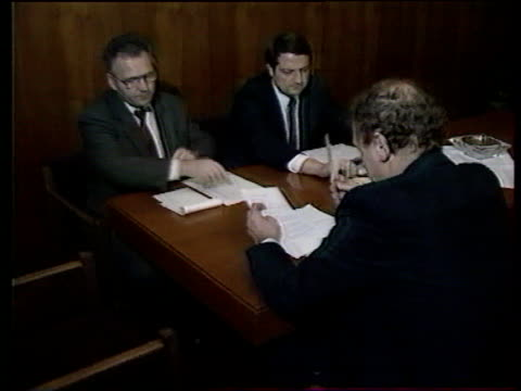 Prague EXT Karel Urbanek waves to press and into Prime Ministers office Urbanek and two unidentified officials seated at table looking at papers and...