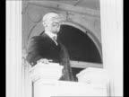US President Woodrow Wilson speaks at event in 1917 / montage German journalists at Versailles in 1919 / hand turns pages of the signed Treaty of...