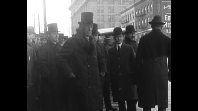 President Woodrow Wilson stands near street in Milwaukee Wisconsin he wears a winter coat and top hat during his visit to discuss his campaign for...