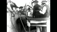 President Woodrow Wilson visits shipyard and watches as unidentified man drives first rivet into a new ship being built at the Alexandria Virginia...