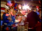 Super Tuesday ITN Texas MS Bush and wife Laura on stage at rally as tickertape falls MS Bush supporters waving posters Bush and wife along on...