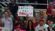 Donald Trump rally in North Carolina Woman supporter holding up 'Latinos For Trump' placard Young man in baseball cap stands filming Trump on his...