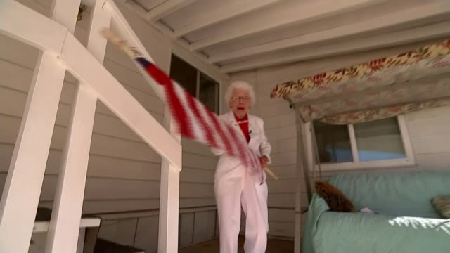 Hillary Clinton campaign USA Arizona EXT Various of Jerry Emmett along on porch unfurling and placing US flag in pole holder and singing SOT