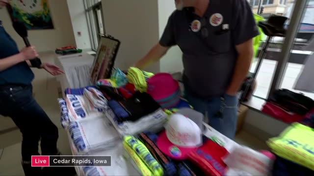2016 presidential hopefuls face first test in Iowa caucus USA Iowa Cedar Falls INT Reporter to camera as looking at politcal souvenirs being sold by...