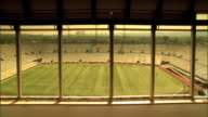 Large panel windows w/ well manicured stadium grass field empty stadium seats beyond lighting towers trees distant city buildings BG DOLLY LEFT From...
