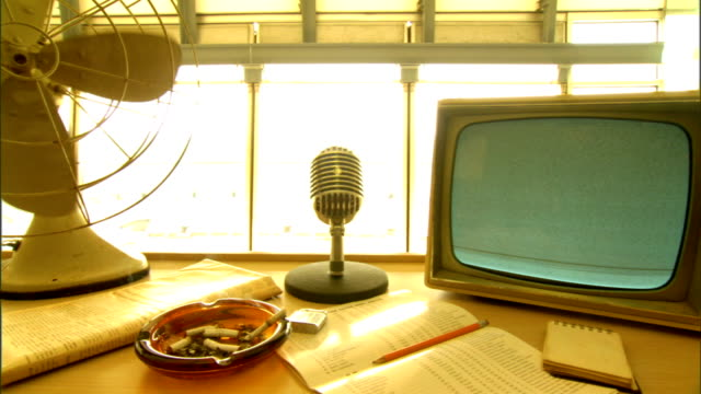 Press desk w/ table fan ashtray w/ cigarette butts burning cigarette almost to filter large chrome table microphone paperwork portable television ON...