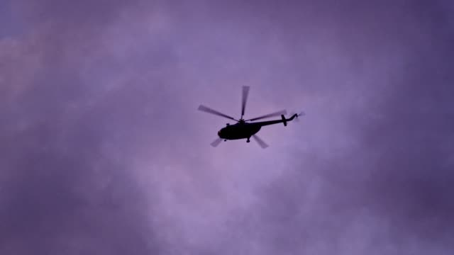 Press Helicopter flying above treetops. Dusk