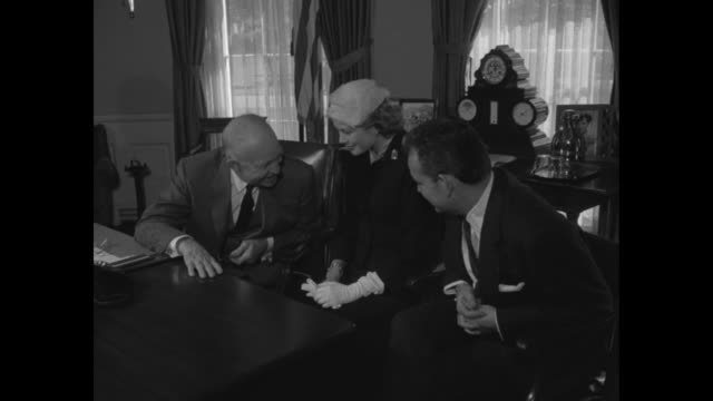 Press photographers snap pictures / Grace Kelly and Prince Rainier sit with President Dwight D Eisenhower behind his desk in the Oval Office he leans...