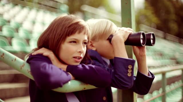 Preteen boy looking away through binoculars, brother nearby, profile