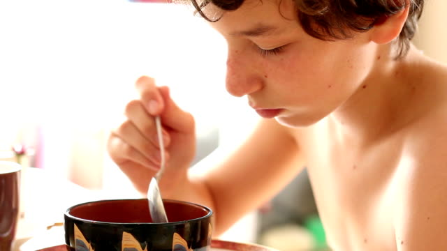 Pre-teen boy playing with and then eating bowl of cereal