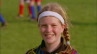 A preteen Caucasian girl wearing a headband and a soccer jersey smiles.