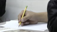 Preteen Latino male right hand writing w/ pencil on paper at table partial left arm jacket FG wall BG Hispanic summer activity after school notes...