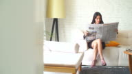 4K:A pretty asian business woman reading the newspaper in her room.