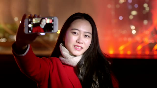 pretty asian girl taking photo with smart phone in modern city at night