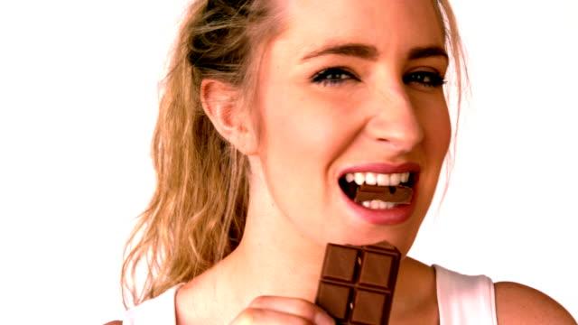 Pretty blonde eating a chocolate bar