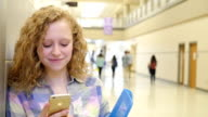 Pretty Caucasian teen girl with blonde curly hair texting on phone in high school