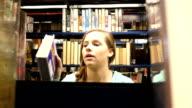 Vrij vrouwelijke Kaukasische home school middelbare schoolstudent zoekt boek in openbare bibliotheek
