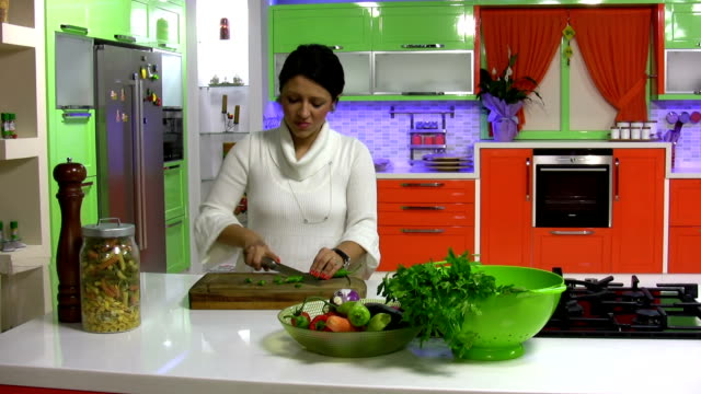 Pretty girl in her kitchen cutting vegetable
