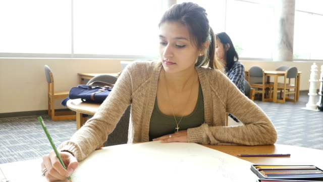 Pretty Hispanic teenage girl works on sketch for art class in school library
