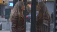 A pretty, mature woman looking into a Brooklyn shop window