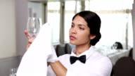 Pretty waitress polishing a wine glass