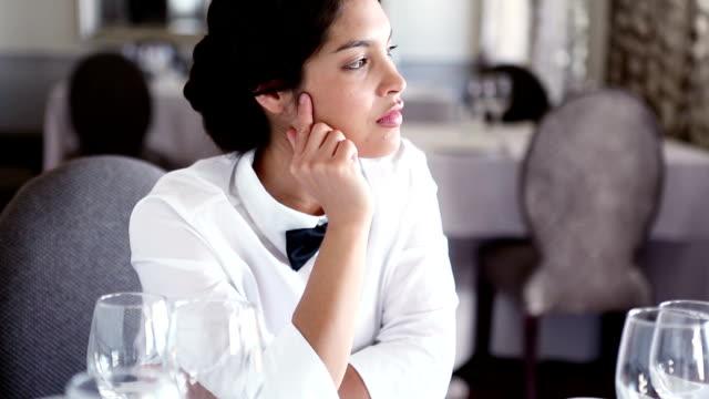 Pretty waitress sitting at set table