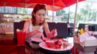 Pretty woman enjoying the taste of grilled steak in restaurant