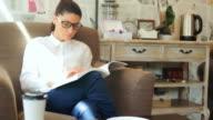 Hübsche Junge Frau beim Buchlesen in einem Teehaus.