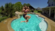 Pretty young woman smiles and jumps into backyard swimming pool