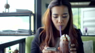 Pretty young woman using smart phone in restaurant