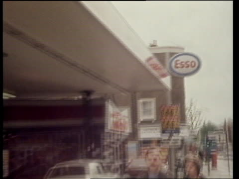 Price rise West London BP sign in forecourt MS Woman fills car London SIGN '146' '148' CMS Dials on pump moving SIGN 'Esso' PULL BACK SIGN 'Esso'...