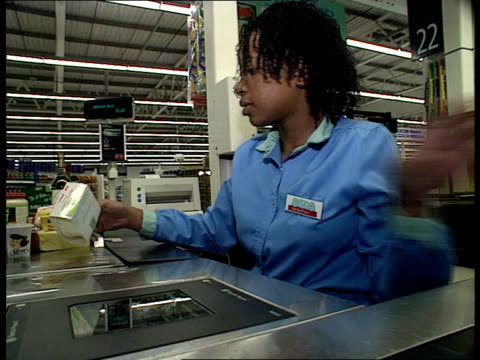 Prices set to rise ENGLAND CS Cartons of milk on ASDA supermarket shelves BV Woman customer away with milk LACMS Black female shop assistant working...