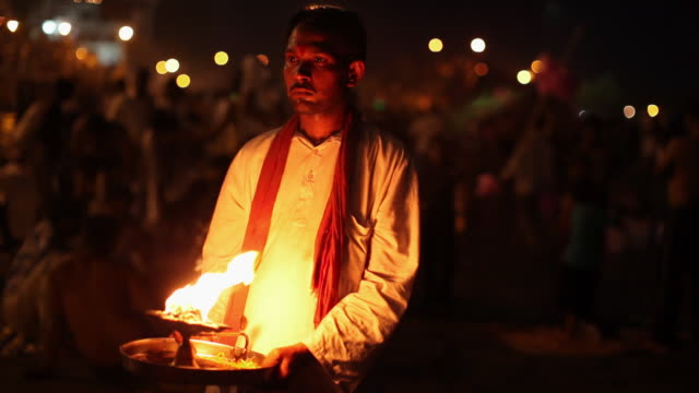 Priest doing aarti at riverbank, Ganges River, Haridwar, Uttarakhand, India