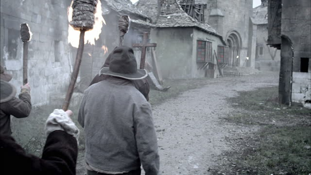 A priest leads villagers with torches as they carry corpses through a village during the Black Plague.
