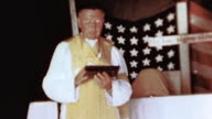 Priest performing service before makeshift altar American flag and simple wooden cross behind