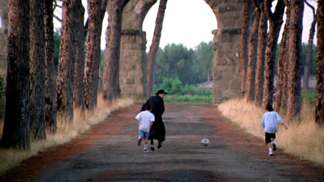 REAR VIEW Priest running + playing soccer with two boys on road / aqueduct in background / Italy