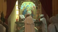 A priest standing at an alter reads from the bible. Available in HD.