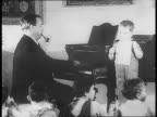 JB Priestly and wife play with small children / Malcolm Muggeridge sits with a child and reads message to him / truck drives to large building in the...
